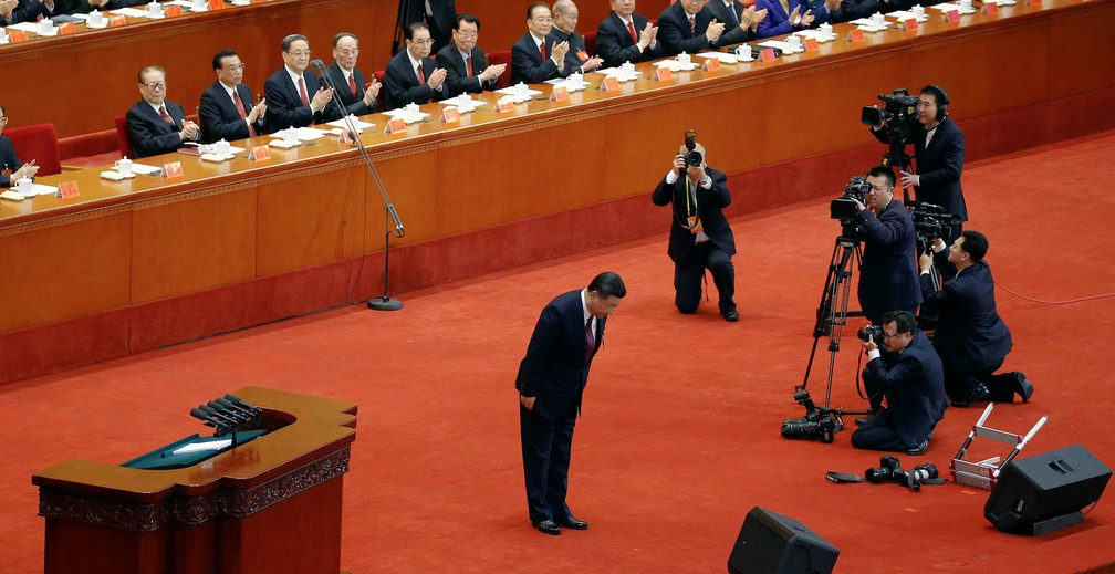 Xi Jinping se curva à plateia durante o congresso do PC chinês (Foto: Jason Lee/Reuters)