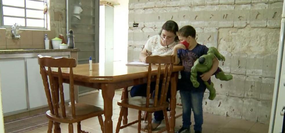 Mãe ajuda Murilo a fazer currículo para entregar na empresa que o pai trabalhava em São João da Boa Vista — Foto: Rodrigo Sargaço/EPTV