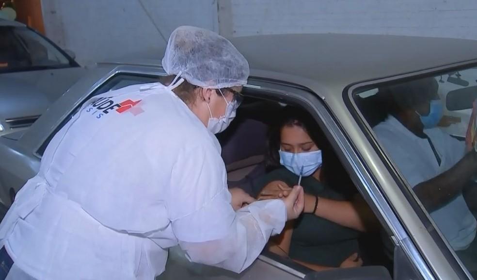 Julia foi uma das jovens que foi até o drive-thru da Ficar receber a dose da vacina em Assis — Foto: TV TEM/Reprodução