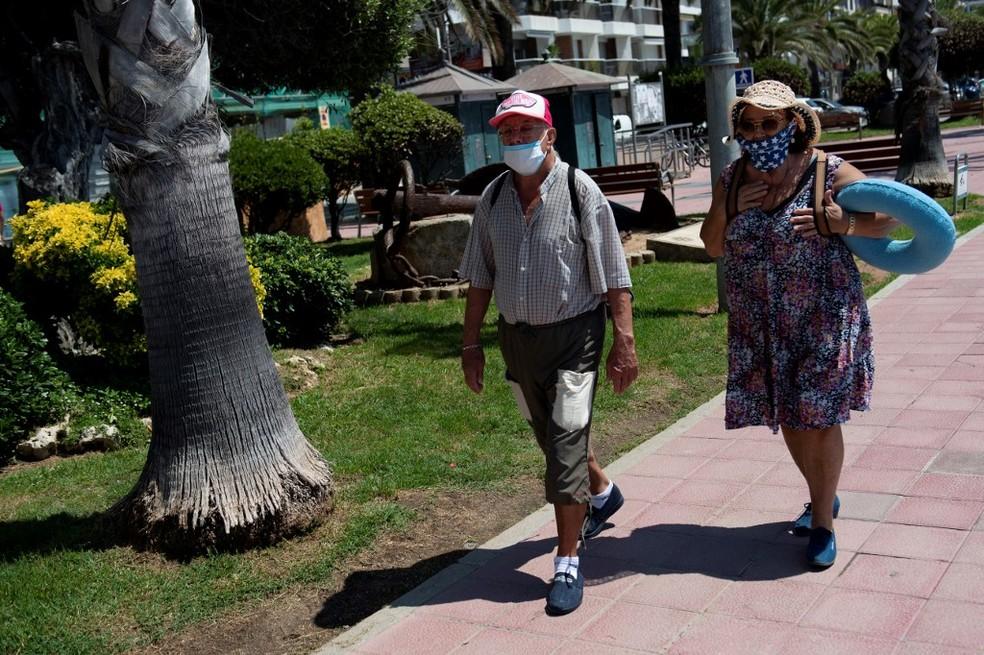 Um casal usando máscaras de proteção para a Covid-19 caminha para uma praia em Lloret de Mar em 22 de junho — Foto: Josep Lago/AFP
