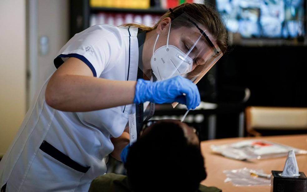 Teste de Covid-19 é aplicado em funcionário de casa de repouso em Bruxelas, na Bélgica, em 18 de abril — Foto: Kenzo Tribouillard/AFP
