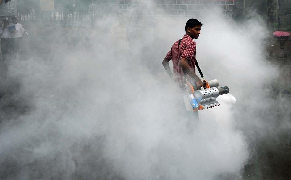 Indiano solta fumaça contra o mosquito da malária em rua de um conjunto residencial em Mumbai, na Índia. (Foto: Punit Paranjpe/AFP)