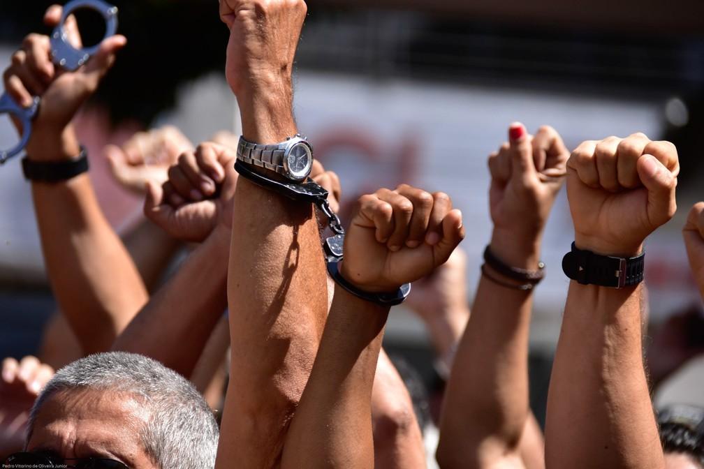 3 de janeiro - Policiais civis do Rio Grande do Norte se apresentam algemados na Delegacia Geral de Polícia (DEGEPOL), em Natal, para serem presos. O Tribunal de Justiça do Rio Grande do Norte considerou a greve que eles faziam desde 20 de dezembro ilegal e determinou a prisão de policiais da ativa e da reserva que incentivem, promovam ou defendam a greve (Foto: Vitorino Junior/Photopress/Estadão COnteúdo)