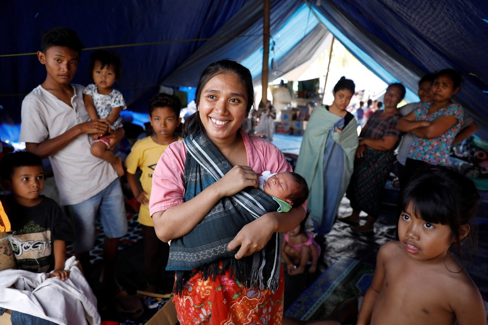 Mãe e sua bebê de apenas três dias estão em abrigo no norte de Lombok, na Indonésia, nesta sexta-feira (10) (Foto: Beawiharta/ Reuters)