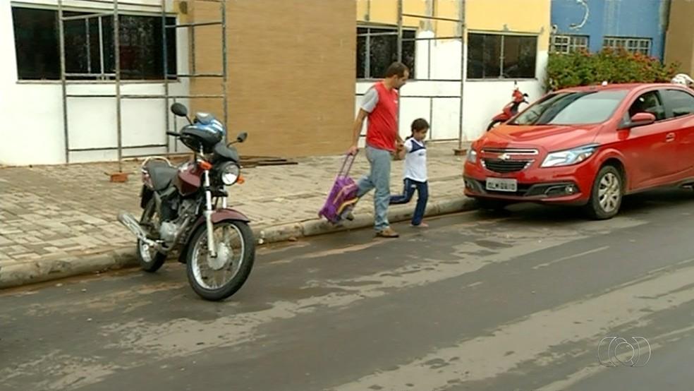 Pai ajuda criança a atravessar rua sem faixa de pedestre (Foto: Reprodução/TV Anhanguera)