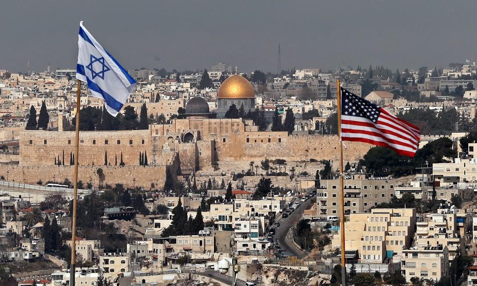 Bandeiras de Israel e dos EUA são vistas no telhado de um prédio em um assentamento israelense em Jerusalém Oriental com a mesquita Domo da Rocha ao fundo  (Foto: Ahmad Gharabli/AFP)