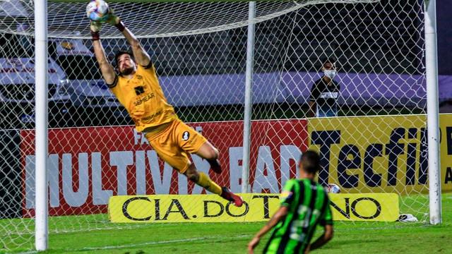 Goleiro do América-MG, Matheus Cavichioli defende chutaço de Hugo, do CRB