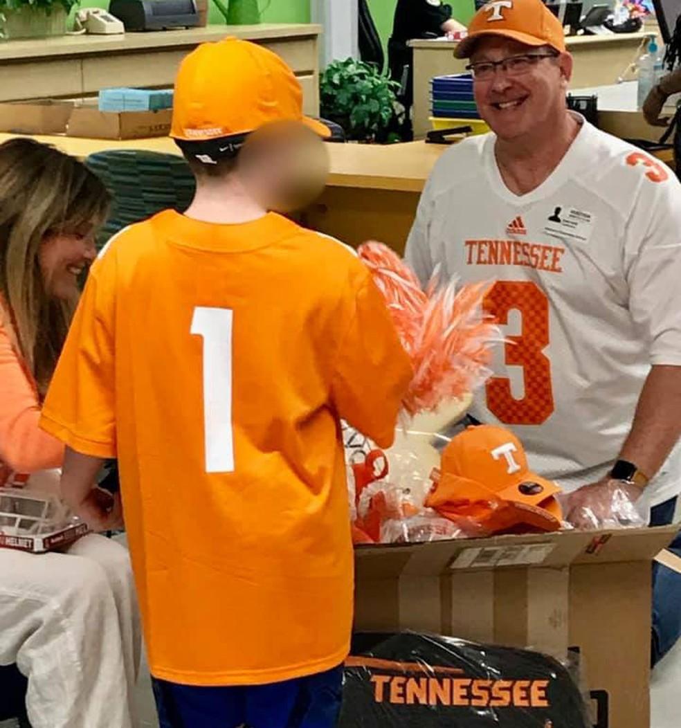 Um representante da Universidade do Tennesse entrega presentes ao menino que criou a versão improvisada da camiseta em sua escola, na Flórida — Foto: Reprodução/Facebook/Laura Snyder