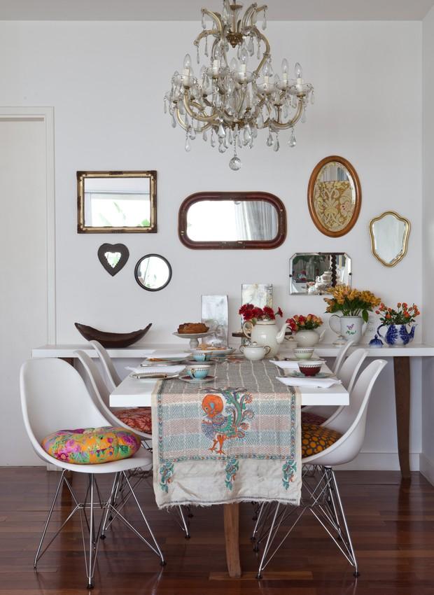 A sala de jantar da designer Ana Morelli tem paredes e móveis brancos, mas está longe de ser um ambiente neutro. Ele ganhou charme com vários espelhos, bules com flores e xícaras coloridas (Foto: Lufe Gomes/Casa e Jardim)