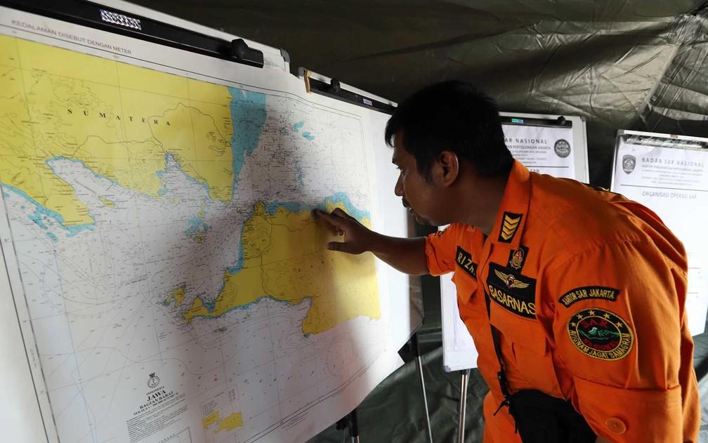Integrante da equipe de resgate aponta para o local onde o voo JT- 610 da Lion Air caiu no mar — Foto: Resmi Malau / AFP