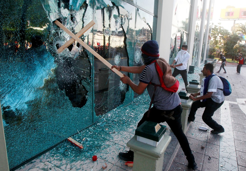 -  Participante de protesto estoura fachada de vidro em Tegucugalpa, em Honduras  Foto: REUTERS/Jorge Cabrera