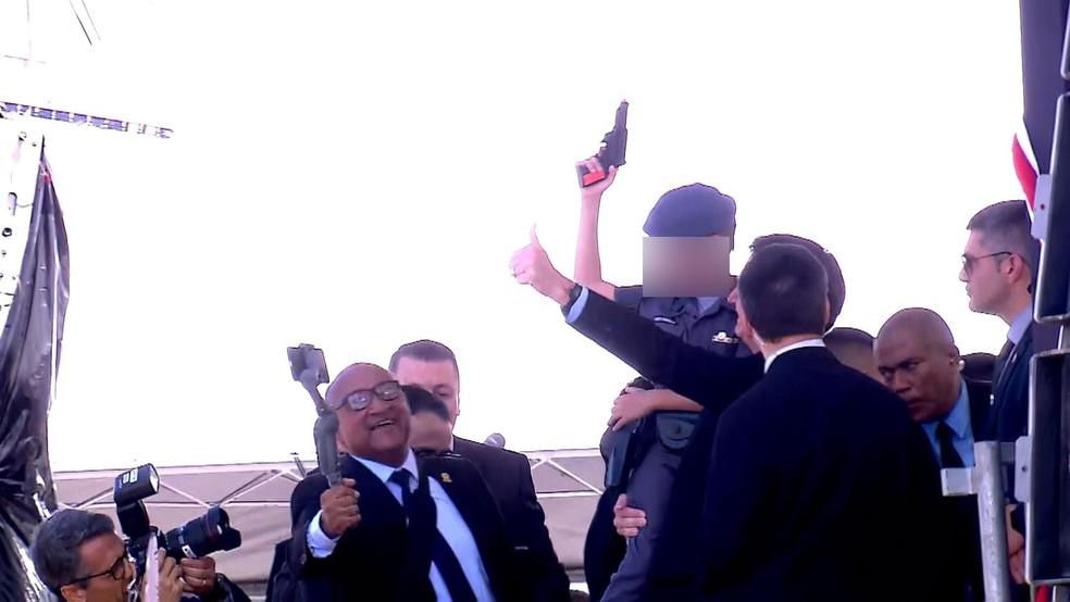 Criança no colo de Bolsonaro aponta arma de brinquedo para o alto durante evento de formação de sargentos da Polícia Militar de São Paulo — Foto: Reprodução/TV Globo