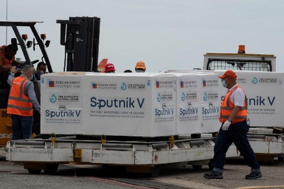 Funcionários do aeroporto venezuelano colocam em um caminhão refrigerado pacotes contendo 100.000 doses da vacina russa Sputnik V contra o vírus COVID-19 no aeroporto internacional Simon Bolivar em La Guaria, Venezuela, em 13 de fevereiro de 2021 — Foto: Yuri CORTEZ / AFP