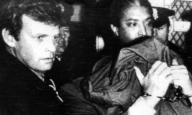 O assassino de John Lennon, Mark Chapman, cobre a cabeça, de mãos algemadas, um dia após o crime