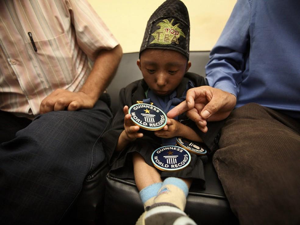 Khagendra Thapa Magar, ex-homem mais baixo do mundo, olha nesta segunda-feira (13) para sua medalha do Livro Guinness de Recordes, enquanto esperava por audiência com o premiê do Nepal, Jhala Nath Khanal, em Katmandu. Ele entregou um documento ao premiê p — Foto: AP