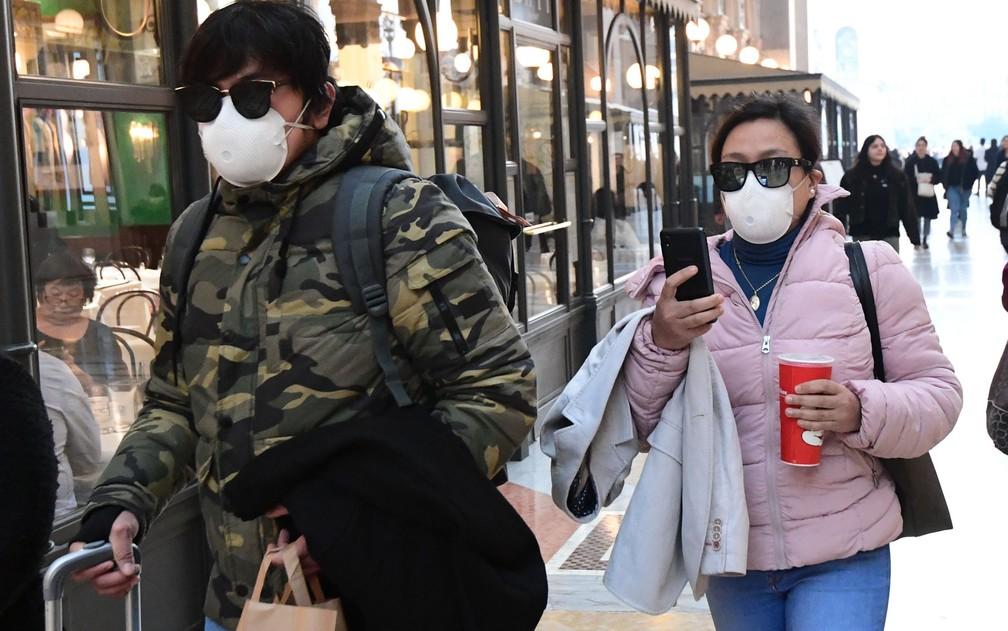 Turistas usam máscaras durante passeio na galeria Vittorio Emanuele II, em Milão, na Itália, na segunda-feira (24) — Foto: Miguel Medina/AFP