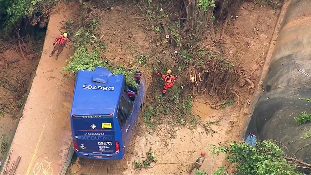 Bombeiros trabalham no resgate de desaparecidos que estavam em um ônibus que foi atingido por um deslizamento na Avenida Niemeyer, no Rio de Janeiro — Foto: Reprodução/TV Globo