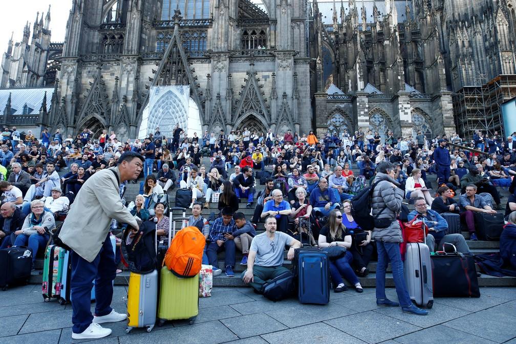Passageiros esperam do lado de fora da principal estação de trem em Colônia, na Alemanha, nesta segunda-feira (15) depois que a estação de trem foi fechada após a tomada de reféns  — Foto: REUTERS / Thilo Schmuelgen
