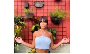 Thaíz Braz posa em cantinho com plantas. Recentemente, a imagem foi usada para brincar com a fase 'namastreta' da confinada do 'BBB' | Reprodução