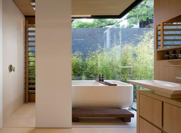 A banheira fica voltada para uma parede de vidro com vista para o jardim (Foto: Filippo Bamberghi)