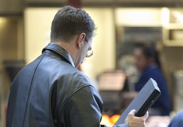 Passageiro guarda notebook na bagagem de bordo, após passar por inspeção antes do embarque (Foto: Tim Boyle/Getty Images)