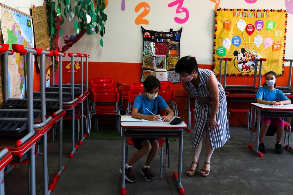 Professora Eliane Conconi conversa com criança em sala de aula da escola Thomaz Rodrigues Alckmin, no primeiro dia de retorno das escolas do estado de São Paulo para atividades extracurriculares — Foto: Amanda Perobelli/Reuters