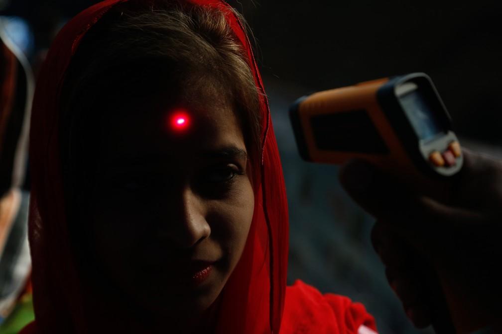 18 de março - Uma passageira tem a temperatura medida por um voluntário em uma estação de trem em Lahore, no Paquistão, como medida para conter o avanço do novo coronavírus (COVID-19) — Foto: K.M. Chaudhry/AP