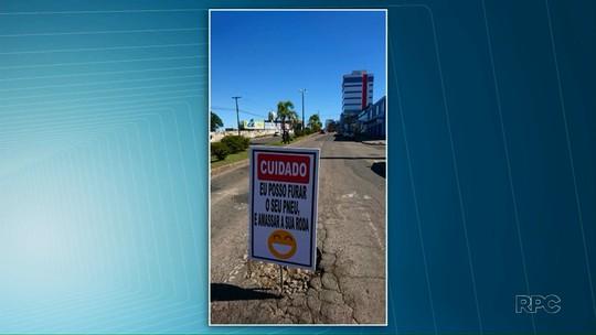 'Posso furar o seu pneu e amassar a sua roda', diz placa instalada em buraco de avenida, em Ponta Grossa
