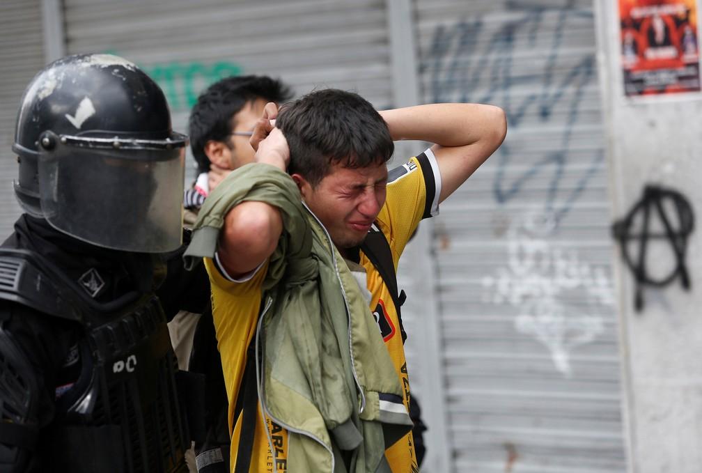 """Polícia prende manifestante no Equador nesta sexta-feira (4), um dia depois de o governo decretar """"estado de exceção"""" — Foto: Daniel Tapia/Reuters"""