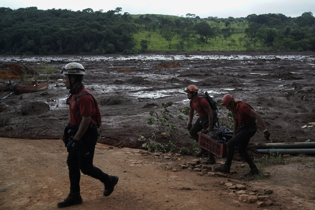 Bombeiros carregam corpo retirado da lama em uma cesta depois do rompimento da barragem da Vale em Brumadinho. — Foto: Leo Correa/AP