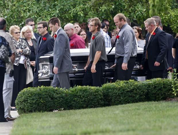 Caixão de Matthew McQuinn, um dos 12 mortos no cinema em Aurora, é carregado após funeral em igreja, neste sábado (28). Quando os tiros começaram, ele teria protegido a namorada e, por isso, levou três tiros. Outros enterros de vítimas do ataque aconteceram durante a semana. (Foto: AP)