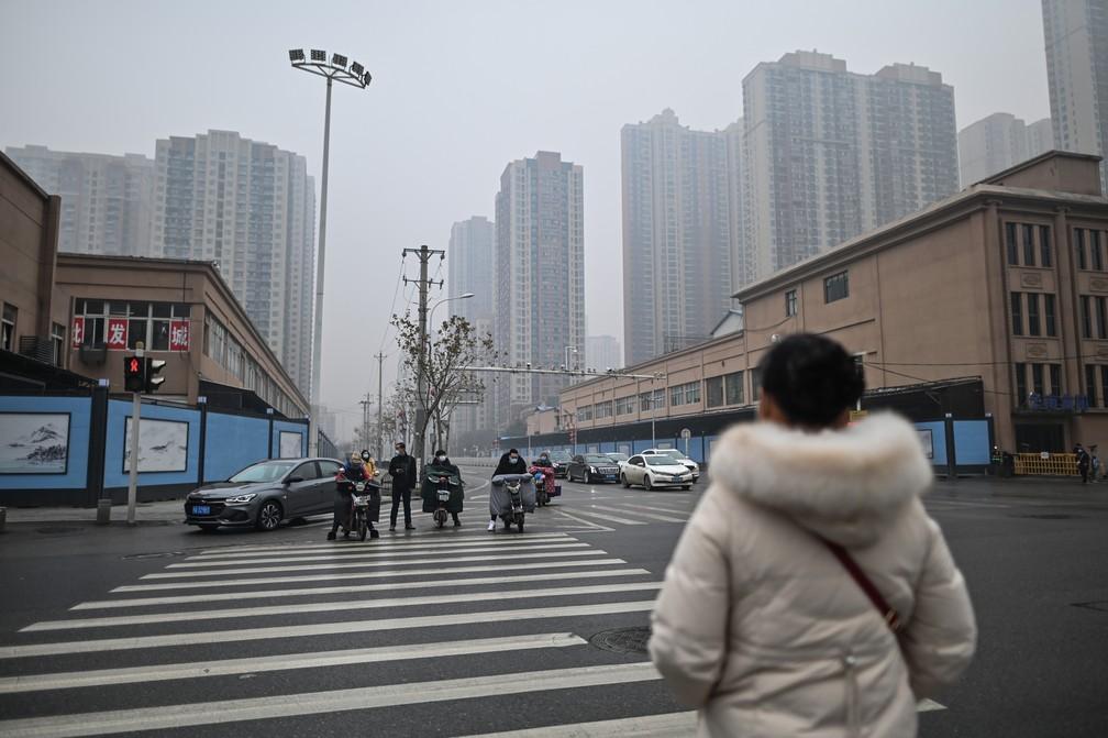 Pedestres caminham em Wuhan, na China, em frente ao mercado de animais fechado onde teria começado o surto de Covid-19; foto de 23 de janeiro de 2021 — Foto: Hector Retamal/AFP