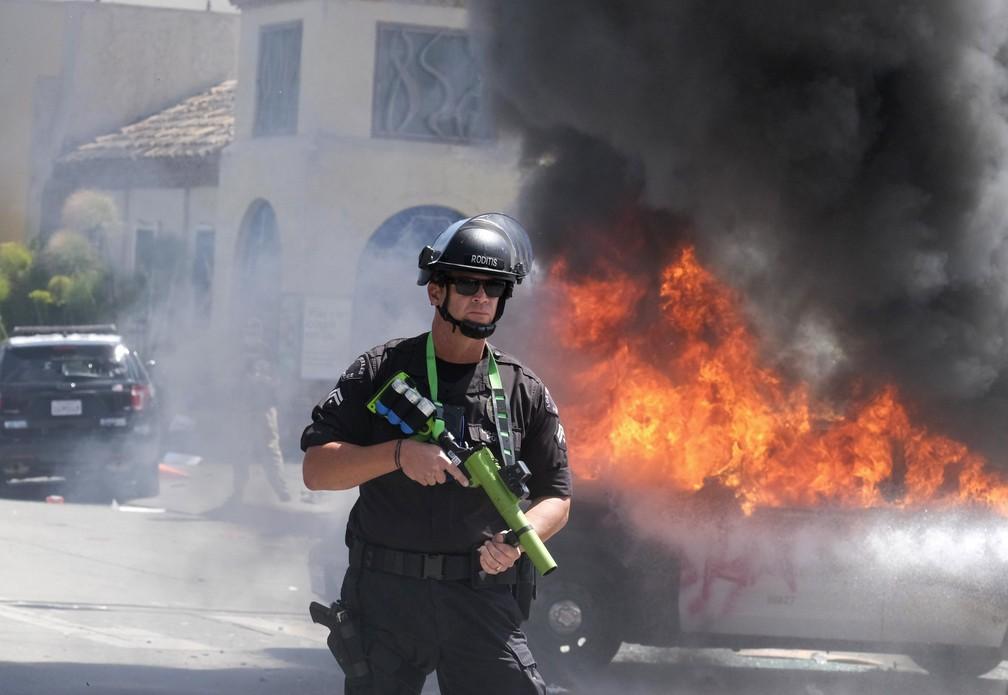 Policial monitora manifestação em Los Angeles após veículo policial ser incendiado neste sábado (30) — Foto: Ringo H.W. Chiu/AP Photo