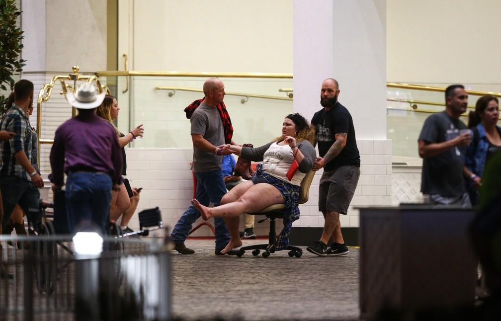 Uma mulher ferida é retirada do local onde um atirador disparou contra uma multidão em um festival de música country em Las Vegas, nos EUA (Foto: Chase Stevens/Las Vegas Review-Journal/via AP)