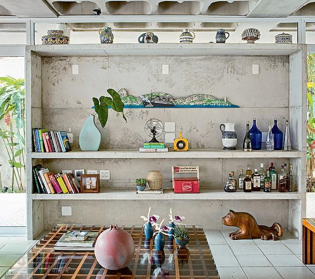 Solta do teto, a estante é uma caixa de concreto. Fechada no alto por caixilho com vidro fixo, tem prateleiras do mesmo material. O projeto é do arquiteto Gustavo Calazans (Foto: Edu Castello/Casa e Jardim)