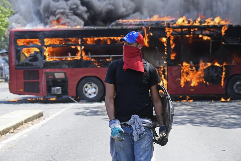 Manifestante caminha diante de ônibus incendiado durante confronto em Caracas, na Venezuela  — Foto: Federico Parra/AFP