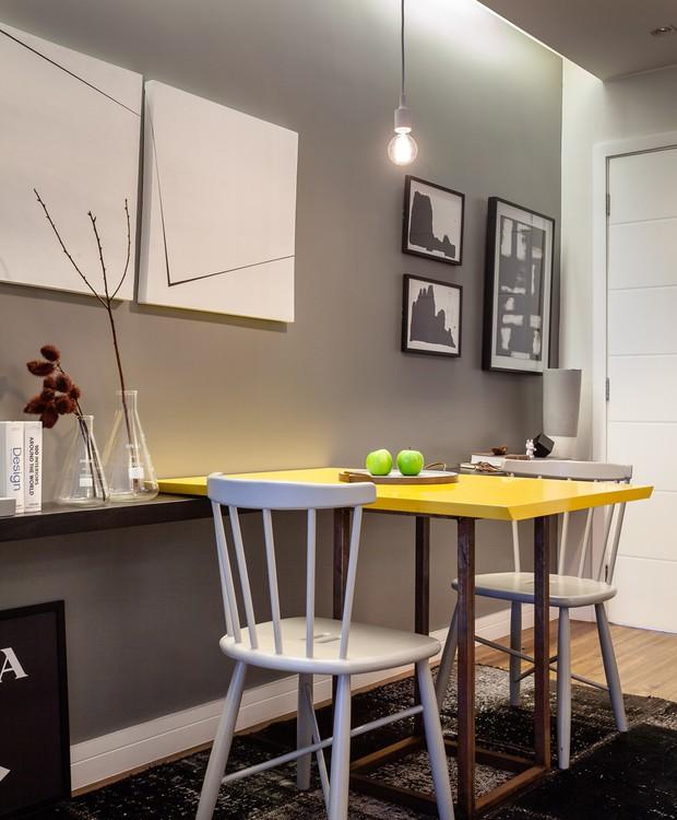 As telas de Leandro Neves se destacam diante da parede cinza. Cadeiras da LZ Studio (Foto: Dhani Borges)