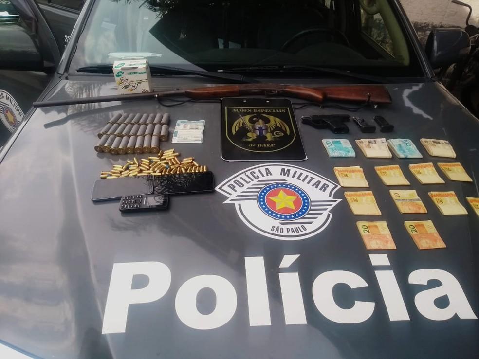 Armas, munições e dinheiro apreendidos na casa onde o homem foragido se escondia — Foto: Baep/Divulgação