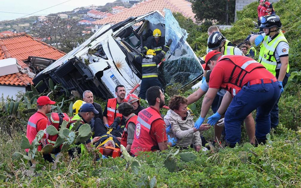Bombeiros ajudam vítimas de acidente com ônibus na região de Caniço, na Ilha da Madeira, em Portugal, na quarta-feira (17) — Foto: Rui Silva/AFP