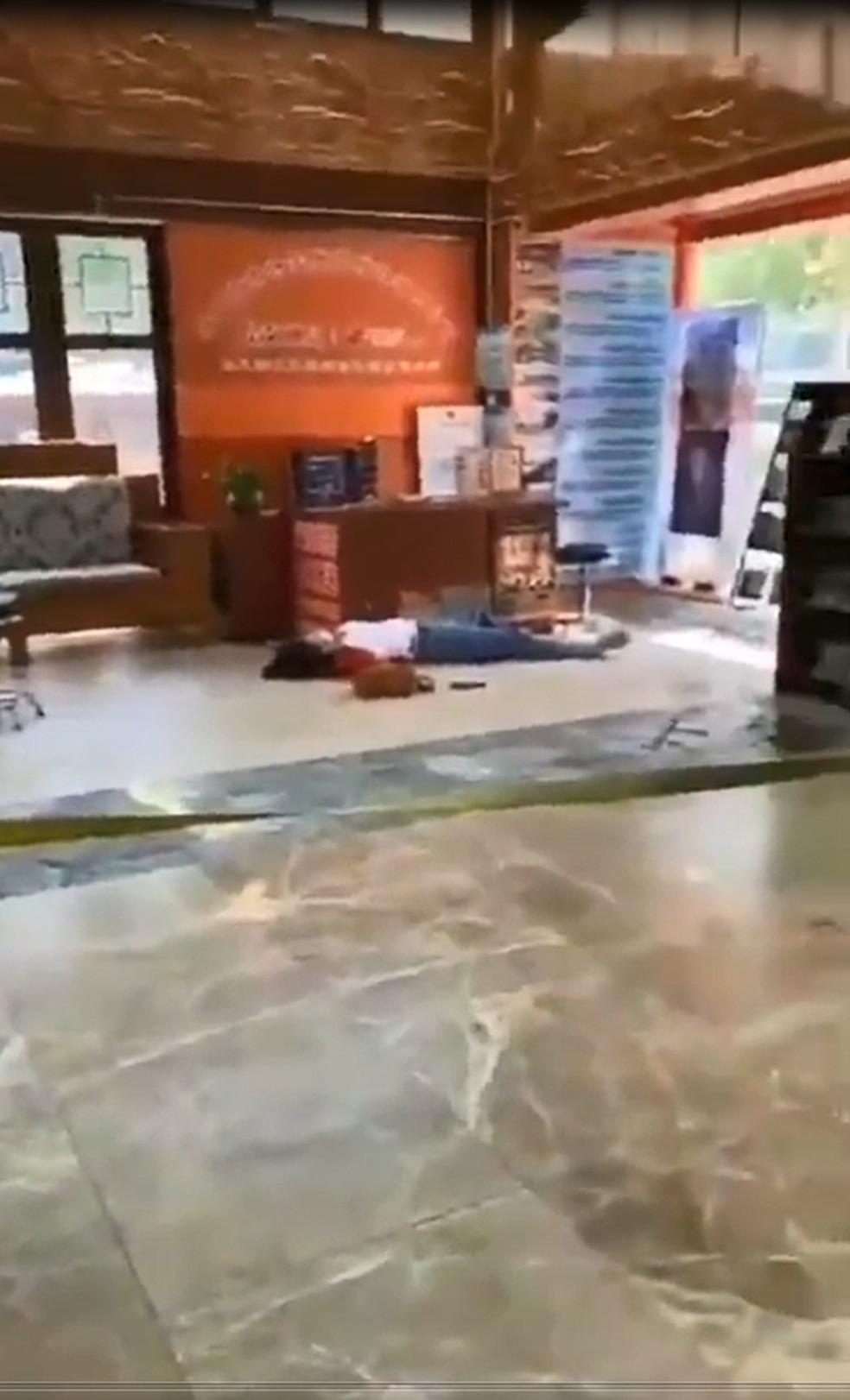 Pessoa caída em hall de prédio  — Foto:  Reprodução