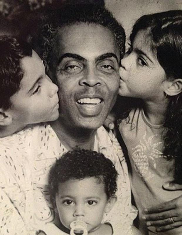 Família grande: em uma foto antiga, que faz parte do livro, Bela dá um beijo no pai, Gilberto Gil, ao lado dos irmãos, Bem e José (no colo). (Foto: Reprodução)