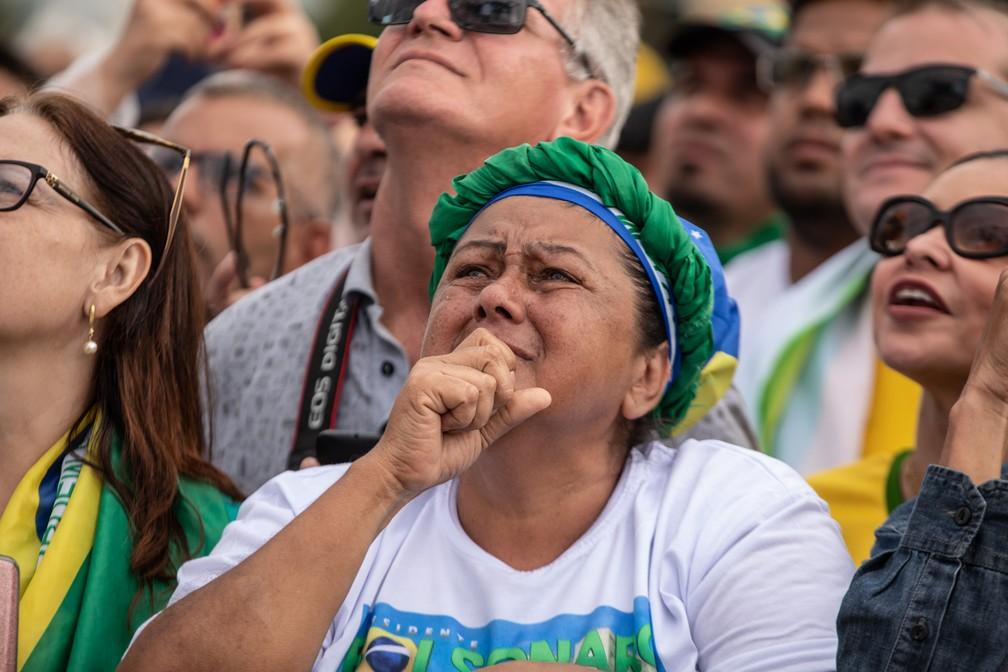 Mulher se emociona na Praça dos Três Poderes durante transmissão da sessão solene de posse em um telão — Foto: Fábio Tito/G1