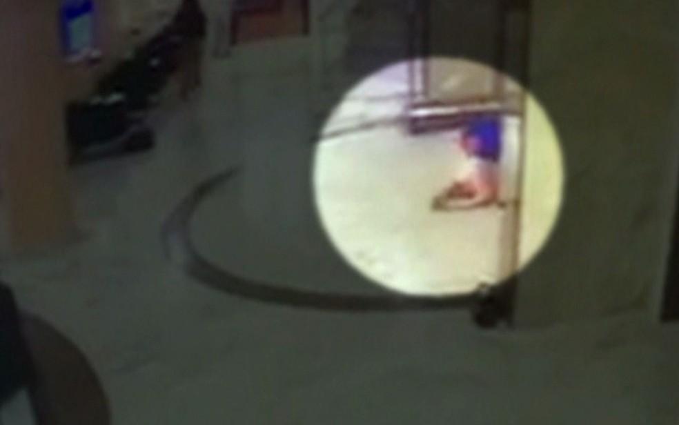 Imagem mostra mulher que foi atingida do lado de fora do hotel caída em frente à porta de entrada (Foto: TV Globo/Reprodução)