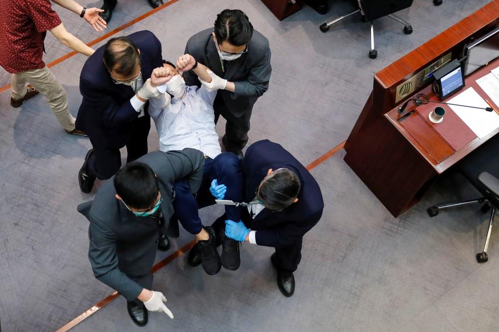 O legislador pró-democrático Raymond Chan Chi-chuen é carregado por seguranças enquanto protesta contra novas leis de segurança durante a reunião do Comitê da Câmara do Conselho Legislativo em Hong Kong nesta sexta-feira (22) — Foto:   Tyrone Siu/Reuters
