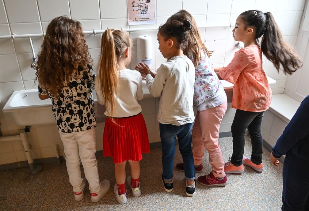 Meninas lavam as mãos antes de entrarem na sala de aula em uma escola primária em Lille, no norte da França, no dia 1º de setembro, primeiro dia letivo em meio à pandemia de Covid-19. — Foto: Denis Charlet/AFP