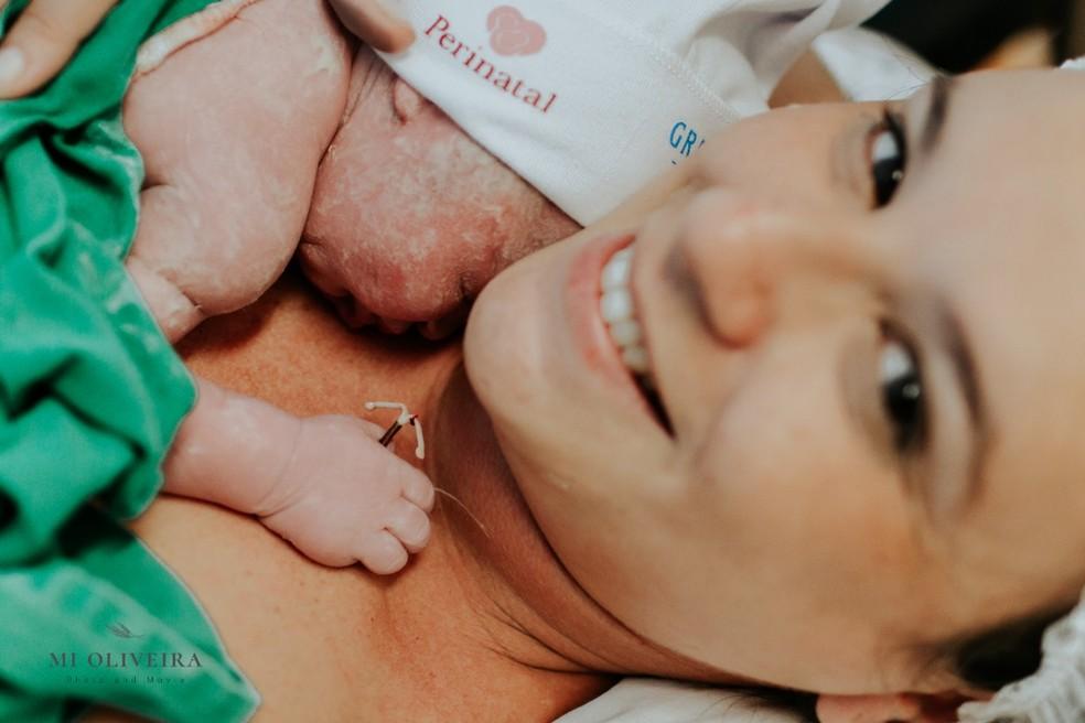Paula com o filho Bernardo segurando o DIU da mãe — Foto: Michelle Oliveira/Divulgação