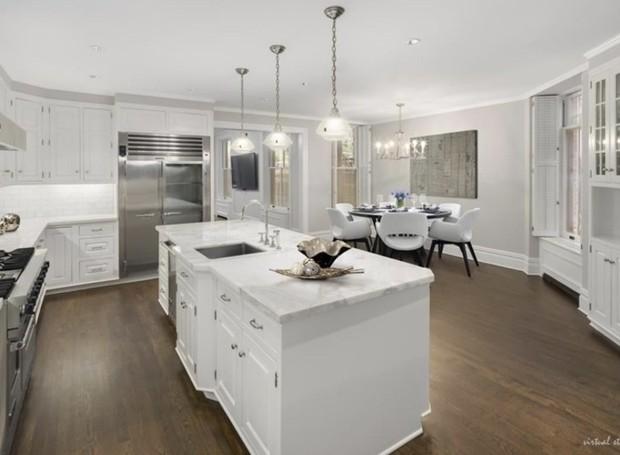 Os armários e bancadas da cozinha são revestidos por madeira branca e mármore (Foto: Trulia/ Reprodução)