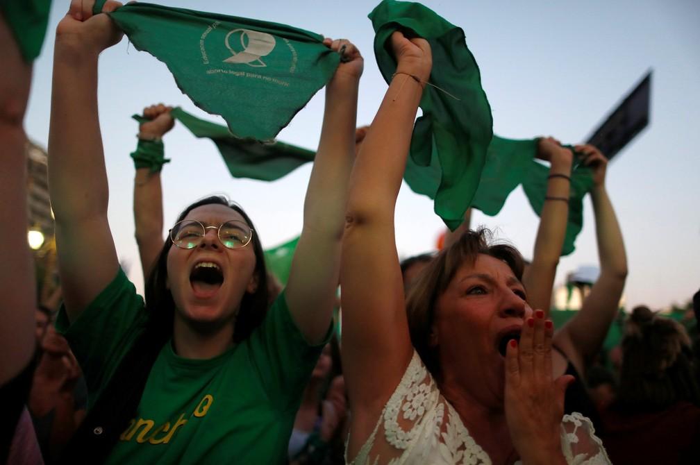 Ativistas seguram lenços verdes, que simbolizam o movimento dos direitos ao aborto, durante uma manifestação para legalizar o aborto em frente ao Congresso argentino, em Buenos Aires em 19 de fevereiro — Foto: Agustin Marcarian/Reuters