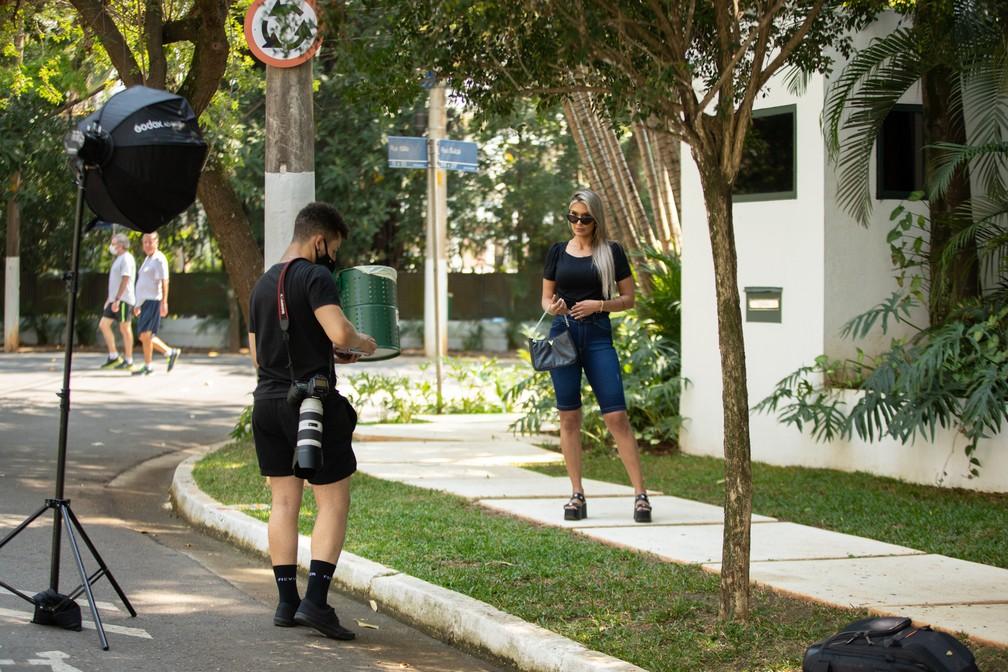 Moradores caminham pelas ruas do Jardim Europa, na Zona Sul de São Paulo, enquanto modelo faz ensaio em frente a mansão.  — Foto: Marcelo Brandt/G1