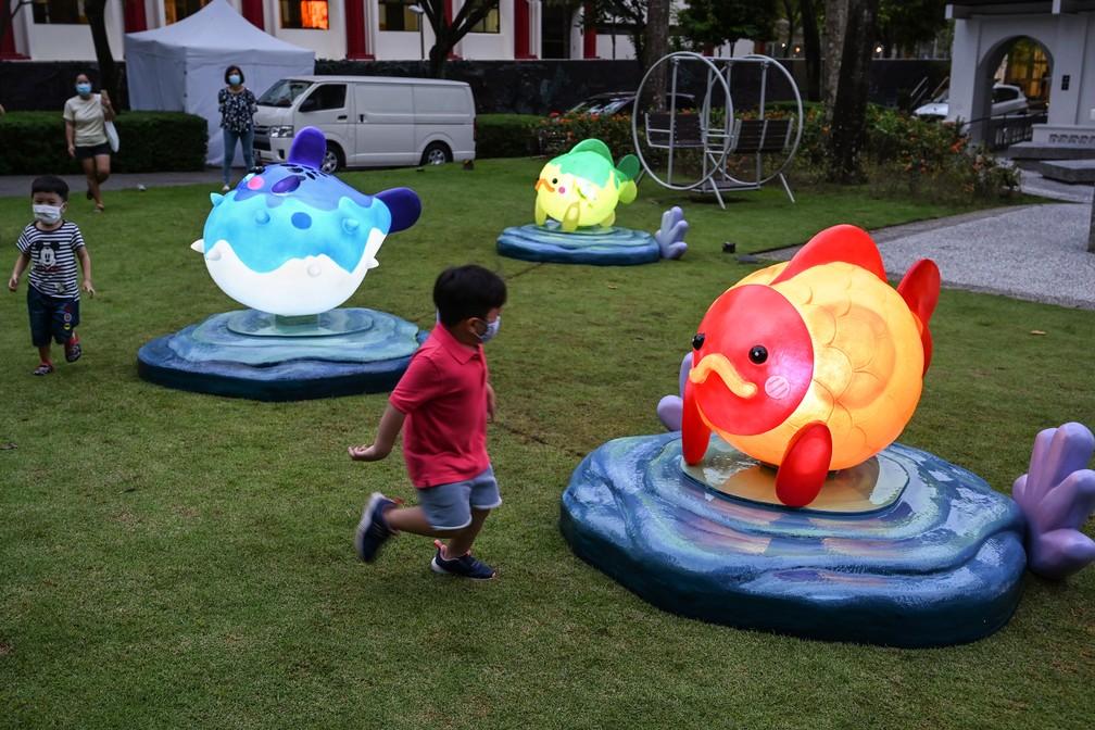 14 de setembro - Adultos assistem crianças brincarem em torno de instalações de lanternas em forma de peixe no Sun Yat Sen Nanyang Memorial Hall, em Singapura  — Foto: Roslan Rahman/AFP